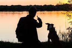 Męski wycieczkowicza i zwierzęcia domowego pies siedzi blisko jeziora przy świtem Zdjęcie Stock