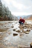 Męski wycieczkowicza obsiadania kamień w rzece Obrazy Royalty Free