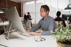 Męski wykonawczy działanie na komputerze w biurze Zdjęcia Royalty Free