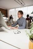 Męski wykonawczy działanie na komputerze w biurze Zdjęcie Royalty Free