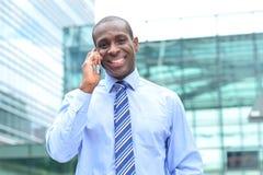 Męski wykonawczy opowiadać na jego telefonie komórkowym Fotografia Stock