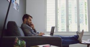 Męski wykonawczy opowiadać na telefonie komórkowym podczas gdy używać laptop w nowożytnym biurze 4k zbiory