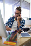 Męski wykonawczy opowiadać na telefonie podczas gdy pracujący przy jego biurkiem Zdjęcia Stock