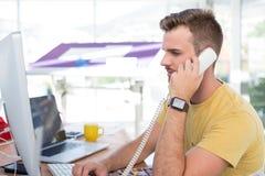 Męski wykonawczy opowiadać na telefonie przy biurkiem Obrazy Stock