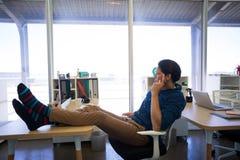 Męski wykonawczy relaksować przy jego biurkiem Zdjęcia Stock
