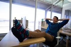 Męski wykonawczy relaksować przy jego biurkiem Obraz Stock