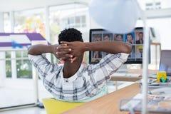 Męski wykonawczy relaksować przy jego biurkiem w biurze Fotografia Stock