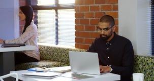 Męski wykonawczy używa laptop w biurowym bufecie 4k zdjęcie wideo