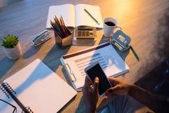 Męski wykonawczy używa telefon komórkowy przy jego biurkiem Obraz Stock