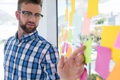 Męski wykonawczy wskazywać przy kleistą notatką w biurze Obraz Royalty Free