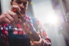 Męski wytwórca egzamininuje piwną butelkę Obrazy Stock