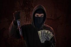 Męski zabójca trzyma nóż i pieniądze Obrazy Stock