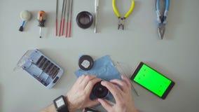 Męskich ręk remontowy obiektyw na popielatym stole zbiory