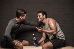 Męskie atlety odpoczywa i conversing przy gym szatnią Fotografia Stock