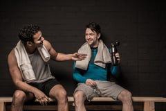 Męskie atlety odpoczywa i conversing przy gym szatnią Fotografia Royalty Free