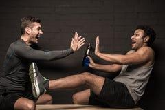 Męskie atlety odpoczywa i conversing przy gym szatnią Zdjęcie Royalty Free