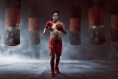Męskie azjatykcie używa rękawiczki boksuje z uderzać pięścią torbę Fotografia Stock