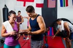 Męskie i żeńskie atlety dyskutuje nad schowkiem Zdjęcia Royalty Free