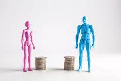 Męskie i żeńskie figurki stoi obok równych stosów monety Fotografia Royalty Free