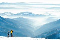 Męskie i żeńskie narciarki dostaje przygotowywający ślizgać się puszek z wierzchu góry wzgórze Obrazy Royalty Free