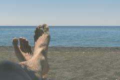 Męskie kosmate nogi garbnikują w słońcu przegapia morze pojęcie relaks, czas wolny, podróż Obraz Royalty Free