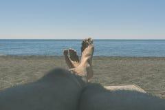 Męskie kosmate nogi garbnikują w słońcu przegapia morze pojęcie relaks, czas wolny, podróż Fotografia Stock