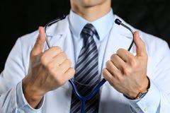 Męskie medycyny lekarki ręki trzymają dalej stetoskop i stawiają Zdjęcia Stock