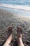 Męskie nogi na otoczaka wybrzeżu morze Selekcyjna ostrość Fotografia Stock