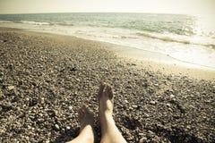Męskie nogi na otoczaka wybrzeżu morze Selekcyjna ostrość stonowany Zdjęcie Stock