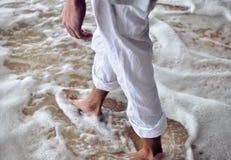 Męskie nogi w nabrzeżnej ocean pianie Obraz Stock