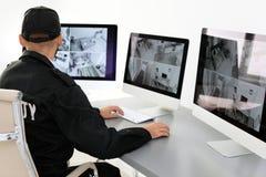 Męskie pracownika ochronego monitorowanie domu kamery zdjęcia stock