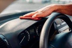 Męskie ręki czyścą samochód, samochodowy deski rozdzielczej froterowanie Fotografia Stock