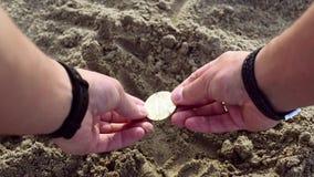Męskie ręki kopią w piasku i znajdują złocistego bitcoin zbiory wideo
