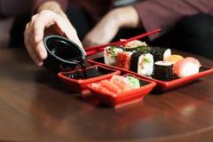 Męskie ręki nalewają kumberland w talerzu czarny zestaw strzały sushi Obraz Stock