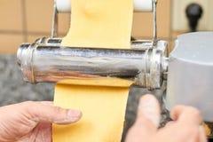 Męskie ręki staczają się ciasto na rolkowej maszynie zdjęcie stock