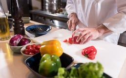 Męskie ręki szefa kuchni rozcięcie tapetują w kuchni Zdjęcie Stock