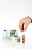 Męskie ręki sztaplowania monety z euro banknotami na tle Zdjęcie Royalty Free