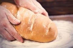 Męskie ręki trzyma chlebowego bochenek na cudownym brown drewnianym plecy Zdjęcia Royalty Free