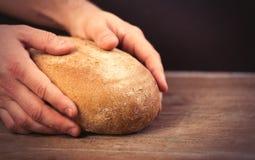 Męskie ręki trzyma chlebowego bochenek na cudownym brown drewnianym plecy Fotografia Royalty Free