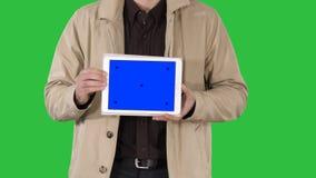 Męskie ręki trzyma pastylkę z błękitnego ekranu mockup na zielenieją ekran, chroma klucz zbiory