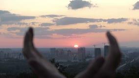 Męskie ręki trzymają słońce przy zmierzchem w Kyiv w lecie w mo zbiory