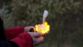 Męskie ręki używają zapalniczkę, zapalają białego papier i rzucają je w zwolnionym tempie daleko od, zbiory