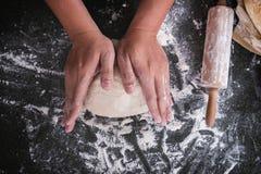 Męskie ręki ugniata ciasto kropiącego z mąka stołem, ręki przygotowywają Obrazy Stock