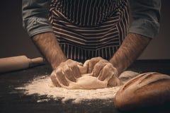 Męskie ręki ugniatają ciasto Zdjęcia Stock
