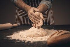 Męskie ręki ugniatają ciasto Fotografia Stock