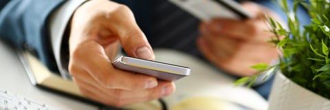 Męskie ręki w kostiumu trzymają kredytową kartę i telefon Zdjęcie Royalty Free