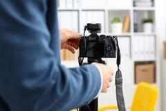 Męskie ręki w kostiumu wspinają się kamera wideo tripod Zdjęcia Stock