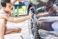 Męskie ręki z piankową tkaniną myje samochodowego koła Czyści koła Używają wodę fotografia stock