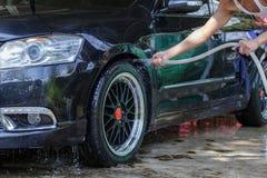 Męskie ręki z piankową tkaniną myje samochodowego koła Czyści koła Używają wodę fotografia royalty free