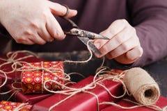 Męskie ręki zawijają Bożenarodzeniowego prezent na drewnianym stole Zdjęcie Royalty Free